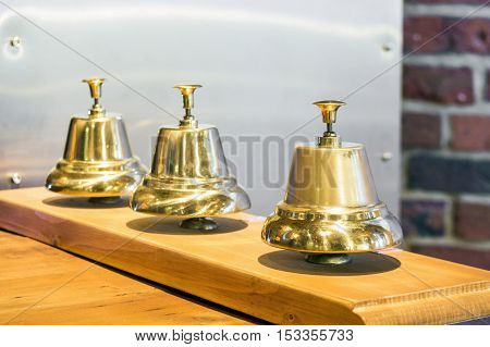 Three shiny golden vintage bells in a row