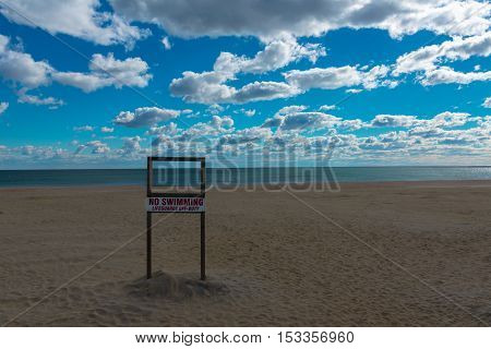 A no-swimming Lifeguards Off-Duty sign on a deserted beach in winter