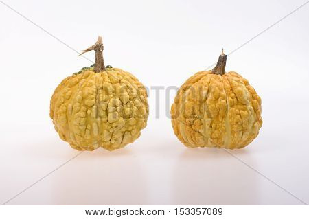 Two decorative yellow pumpkins on a white background