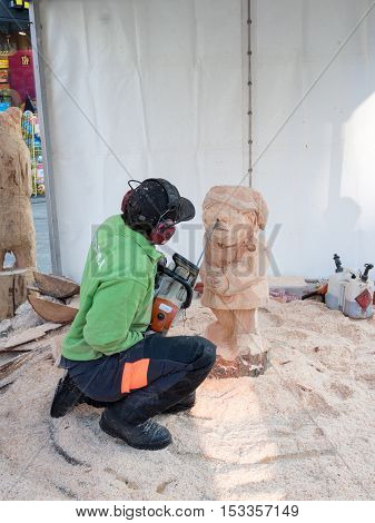 ALMERE, NETHERLANDS - 23 OCT. 2017: Wood carving artist in the townsquare of Almere makes a sculpture of a gnome. Once a year street artists gather to show of their skills to the public in the city.