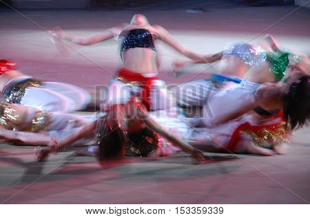 Unrecognized female belly dancers with colorful costumes on stage