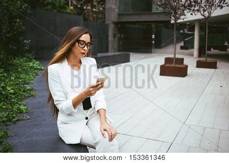 Attractive young woman with long hair in stylish suit is sitting and holding a mobile phone while sitting near office building and reading and writing messages. Copy-space to your text and design