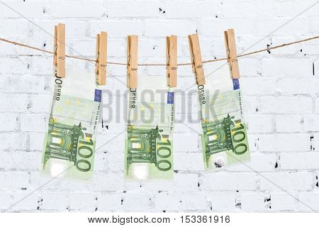 100 Euro Banknotes Hanging On Clothesline On White Brick Wall Background.