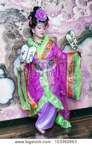 Portrait Of Young Chinese Female In Traditional Dress With Fans, Full Length Against Marble Wall Bac