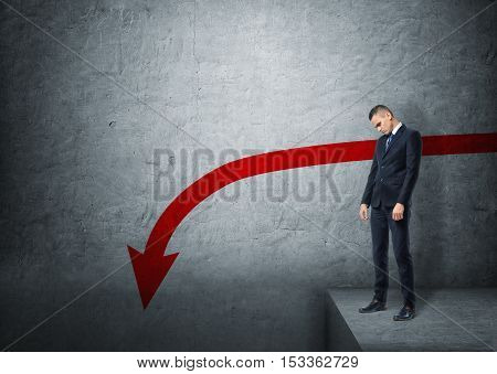 Upset businessman standing on the edge of abyss on the background of concrete wall with red arrow going down. Slump and recession. Stock market plunge. poster
