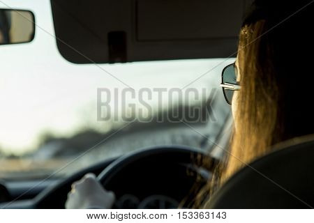 Rear view of woman with sunglasses driving her car