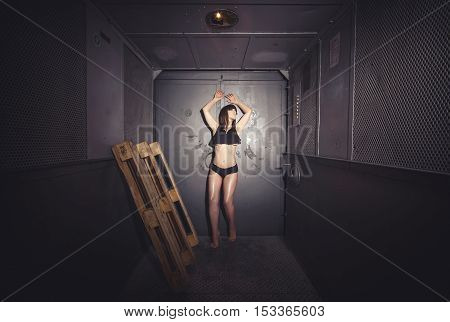 Young, athletic and beautiful woman standing in old, retro elevator with pallets. Dark color toned picture.