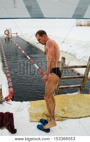 Tyumen, Russia - February 5, 2005: The club of winter swimming holds competitions in the 25 meters ice-hole. The man left an ice-hole after a heat