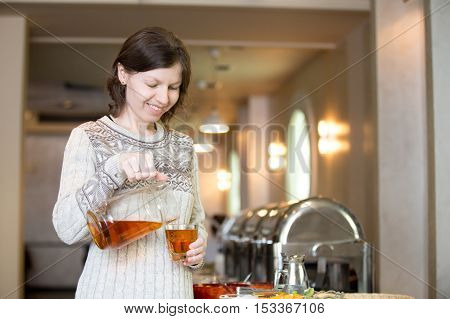Portrait of young happy smiling woman pouring herself a drink from glass pitcher at self-catering breakfast in hotel restaurant