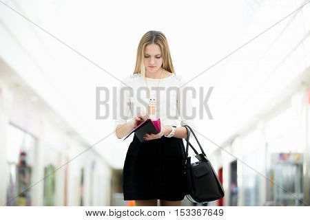 Depressed young female walking in shopping mall looking for cash in her wallet not enough lost money broke