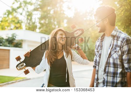Couple carrying long bord and enjoying time outdoors.