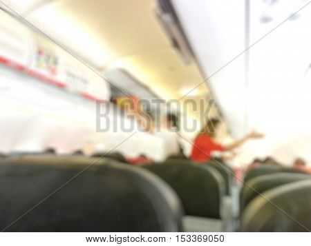 Blurry services provided by airline staff. Flight attendant serving passengers on the plane