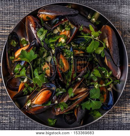 Boiled mussels in pan cooking dish with herbs butter parsley garlic.