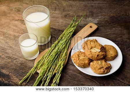 Almond Cookies with rice milk and ear of rice on old wooden table for breakfast for vegetarian festival with warm light background.
