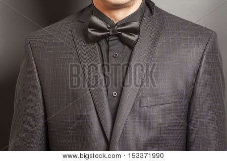 Man in Checkered suit and black and black bow tie on gray background