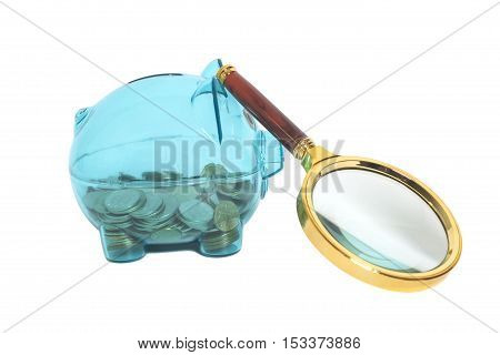 Glass Piggy bank with coins and magnifying glass isolated on white
