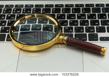 Laptop Computer With Magnifying Glass close up