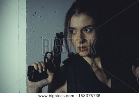 Actress brunette girl with gun in a garage in attitude shoot, dressed in bulletproof vest