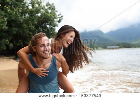 Two young people playing having fun laughing in love. Interracial couple piggybacking, boyfriend carrying Asian girlfriend doing piggyback on hawaiian beach in Kauai, Hawaii travel vacation.