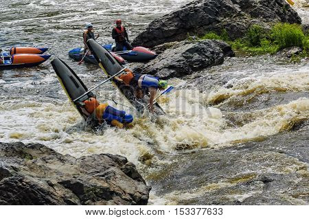 Beklenischevo, Russia - June 12, 2005: The place with the Iset River rapid current, a so-called threshold the Revun - Howler. Woman on sports catamaran for two on water threshold