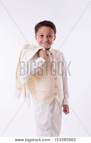 Young First Communion boy smiling with his jacket over his shoulder on white background