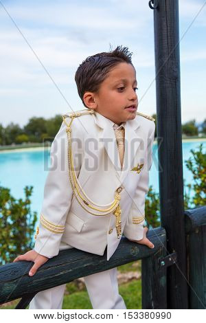 Young boy with white sailor suit leaning on a wooden fence in his First Communion