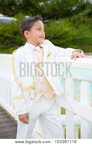 Young boy with white sailor suit leaning on a white wooden fence in his First Communion
