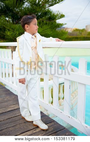 Young boy with white sailor suit leaning on a white wooden fence over a bridge in his First Communion
