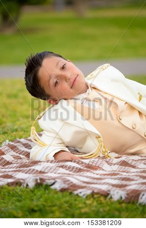 Young boy with white sailor suit in his First Communion lying on a blanket over the grass. Shallow depth of field.