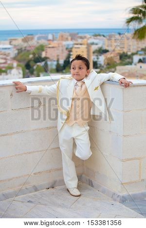 Young boy with white suit leaning on a wall in his First Communion.