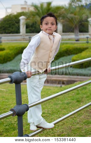 Young First Communion Boy Leaning On A Metal Fence