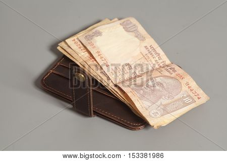 Brown leather wallet with Indian rupee currency on gray background