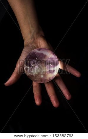 Female hands hold crystal ball with starscape for fortune telling background