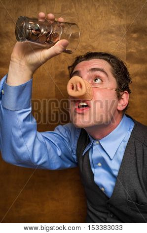 Silly pig man drinking lose change from a glass