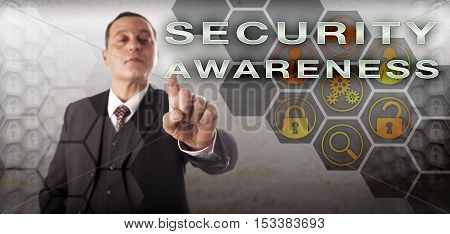 Perky and assertive business manager is activating SECURITY AWARENESS on a touch screen. Information technology concept and business metaphor for knowledge of computer security in an enterprise.