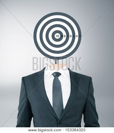 Target-headed businessman on grey background. Targeting concept