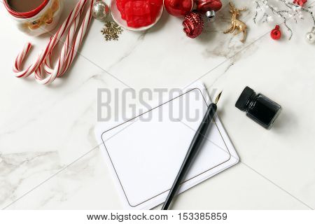 Over head flat lay desktop of Christmas items. Blank stationary, pen and ink, candy, cocoa, and tree trimmings in red and white.