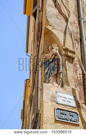 Rue du Felibre Caut street with vinntage Santa Maria statue on its corner in the center of Aix-En-Provence on a warm summer day