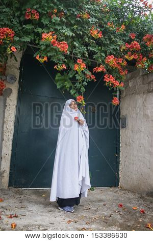 Beautiful Muslim woman in front of her house