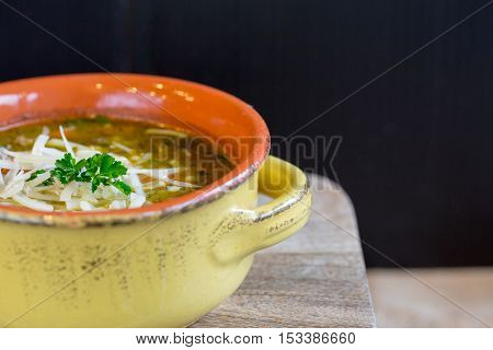 Bowl of vegetable soup in a yellow and orange crock on a wooden board with copy space on right