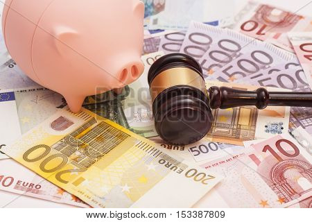 Euro banknotes with court gavel and piggy bank