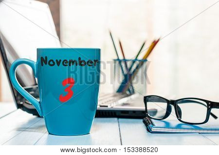 November 3rd. Day 3 of month, calendar on morning blue cup with coffee or tea, student workplace background. Autumn time.