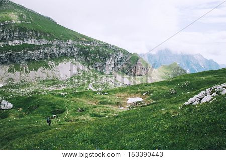 Travelers or hikers in the mountains in the National Park Triglav. Nature landscape. Amazing view on Alps: valley and mountains at summer. Mangart Julian Alps Slovenia.