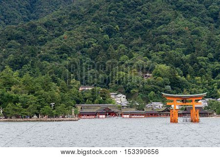 Hiroshima Japan - September 20 2016: Iconic vermilion Torii in front of Itsukushima Shinto Shrine set against the jungle top hill on Miyajima Island. Seen from on the Inland Sea.