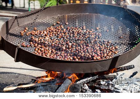 Chestnuts roasting in enormous pan over the fire.
