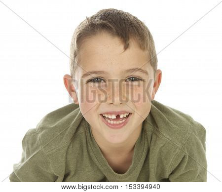 Cute little boy with a missing tooth on a white background.  He is leaning in towards the camera and smiling.