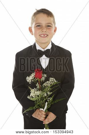 Handsome little boy on a white background with a tuxedo and a long stemmed red rose