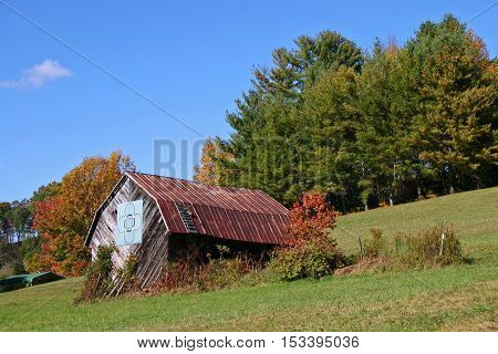 a rustic barn with a quilt pattern, in autumn