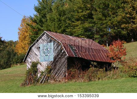 a rustic barn with a rusty roof and a quilt pattern, in autumn