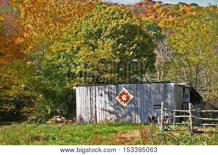 a small shed with a quilt pattern set in among trees with changing colors in autumn